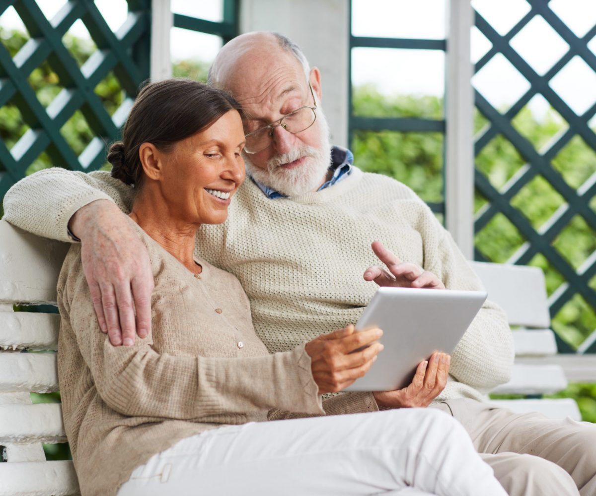Affectionate seniors using tablet for video talk with friends